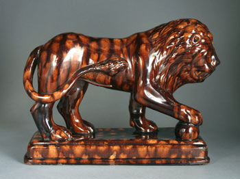 AP/456 Treacleware brown glazed earthenware lion figure, English. treacleware.co.uk (Rockingham ware)